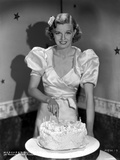 Margaret Sullivan smiling in White Blouse while Slicing Cake