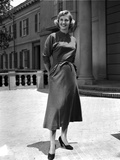 Lola Albright smiling and standing in a Dress