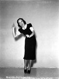 Jane Wyman Posed in Black Velvet Short Sleeve Dress with White Ruffle Collar and Sleeves while Hand