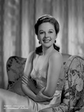 Susan Hayward sitting on a Printed Couch in Silk Dress