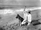 Pola Negri sitting on a Sand with a Dog