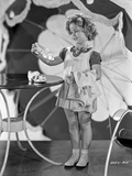 Shirley Temple Holding a Shoe in White Dress