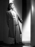 Priscilla Lane Leaning on Wall Pose wearing Dress with Coat