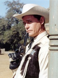 Larry Hagman smiling in Sheriff Uniform Holding a Pistol