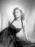 Susan Hayward sitting in a Black Halter Dress