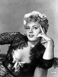 Shelley Winters sitting on Chair in Black Sheer Lace Elbow Ruffle Long Sleeve Dress
