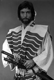 Richard Chamberlain standing in Swordsman Attire With Sword