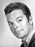 Russ Tamblyn Posed in Black Suit With White Background