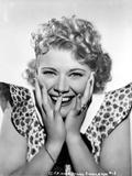 Penny Singleton smiling with Hands on Face in polka dot Dress Portrait with White Background
