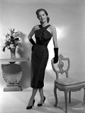 Vera Miles posed standing in a black  ankle length  halter dress and gloves  while leaning onto a c