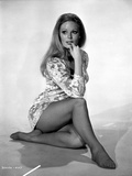 Veronica Carlson photographed sitting on floor  with elbow resting on raised knee and bitting finge