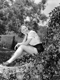 Vera Zorina sitting on vine covered rock  with her head leaned into her head  smiling away from the