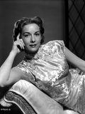 Vera Miles laying on a chaise lounger wearing oriental dress  with head propped into her hand