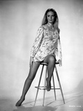 Veronica Carlson posed sitting on stool with one foot resting on the foot rest  wearing floral dres