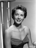 Vera Miles wearing a sleeveless  sweetheart designed bodice accentuated with drop earrings and neck