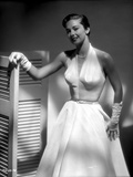 Vera Miles photographed wearing an elegant belted   white organza  deep v-neck  sleevless gown and