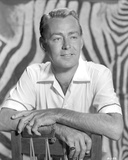 Alan Ladd smiling and posed on the Chair in Black and White Portrait