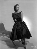 Vera Miles propped on the edge of a chaise lounger  wearing black  sleeveless gown  black gloves an