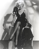 Alice Faye sitting on the Table wearing a Black Dress