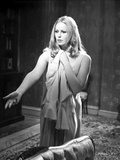 Veronica Carlson standing with arm raised and hand out  clutching a jacket to her chest