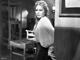 Veronica Carlson clutching corner of the wall  wearing black skirt and pleated draping top