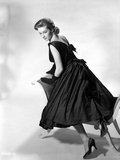 Vera Miles kneeling onto a chaise lounger  looking behind her shoulder  wearing a black  sleeveless