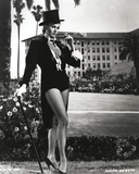Anita Ekberg standing with a Cane wearing a Black Suit in Classic Portrait