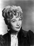 Shirley MacLaine Portrait in Black Short Sleeve Ruffled Dress and Dangling Hoop Earrings