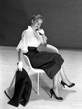 Vera Miles casually posed sitting in a white chair  wearing white chiffon top