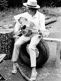 Bob Dylan Seated on Wheel Playing Guitar wearing White Long Sleeves and Slippers