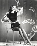 Janet Leigh sitting on Thin Metal Chair in Black Silk Belted Sleeveless Dress