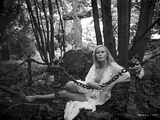 Veronica Carlson a white  chiffon  ruffled robe  while laying on the ground in the forest