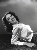 Loretta Young posed Curly Hair Lying with a White Long Sleeves and Black Skirts