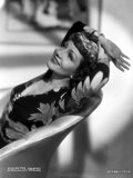Claudette Colbert sitting in Floral Dress with Two Hands on Head