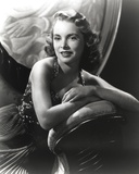 Janet Leigh sitting on the Couch in Black Velvet Strap Dress with Arms Rest on the Chair Arm