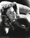 Paulette Goddard smiling while Lying on Couch in Glitter Dress Portrait