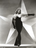 Anita Ekberg Pointing Her Left Hand with a Huge Star in Background in Classic Portrait