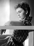 Jean Simmons Leaning Back in Checkered Short Sleeve Shirt with Left Arm Rest on Top of a Railing