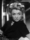 Constance Bennett on a Turtle Neck Top with Brooch sitting and Leaning Portrait
