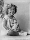 Shirley Temple wearing a House Dress and Holding a Doll in a Classic Portrait