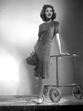 Jean Parker Posed in Grey Short Sleeve Linen Dress and White Shoes with Hands on a Wheeled Table