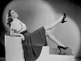 Susan Hayward sitting and Leaning in Skirt with High Heels
