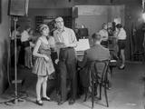 Al Jolson standing with a Woman Near the Piano in a Classic Movie Scene