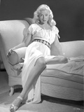 Gloria Grahame Siting on Table wearing Silver Gown