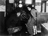 Buster Keaton sitting with Lady wearing a Printed Dress