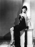 Maria Montez sitting in Black Dress with Leg's Cross