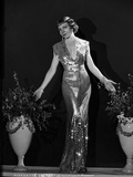 Claudette Colbert standing in Glossy Dress with Palms Open