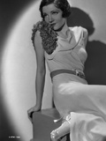 Claudette Colbert sitting in White Dress with Heels