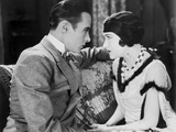 Gloria Swanson Staring with a Guy wearing Formal Outfit