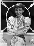 Claudette Colbert smiling in Floral Dress with Arm's Cross